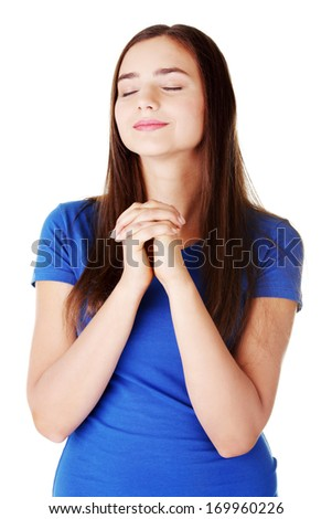 Young beautiful woman is praying. Isolated on white. - stock photo