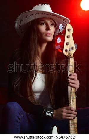 Young beautiful woman is sitting on stage with a bass guitar - stock photo