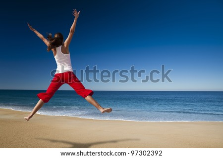 Young beautiful woman jumping in the beach - stock photo