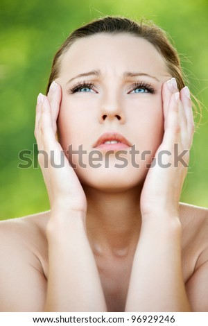 Young beautiful woman keeps hands for head and looks upwards at summer green park - stock photo