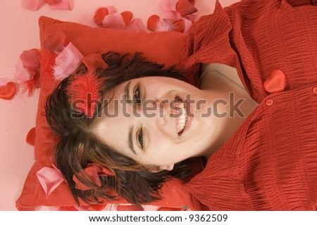 young beautiful woman laying on a red pillow - stock photo