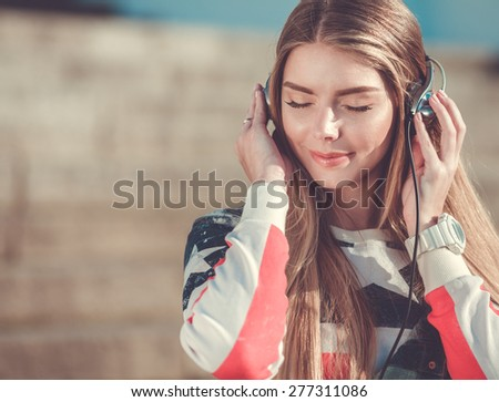 Young beautiful woman listening music on headphones outdoor - stock photo