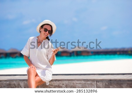 Young beautiful woman listening to music on wooden bridge - stock photo