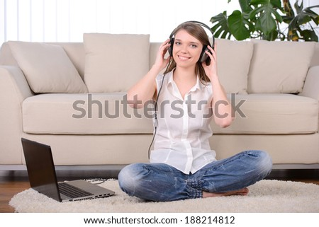 Young beautiful woman listening to music with headphones in their homes - stock photo