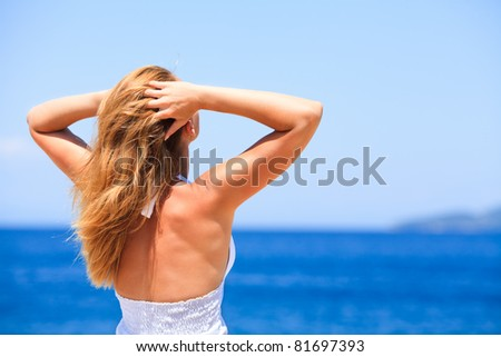 Young beautiful woman looking at the sea