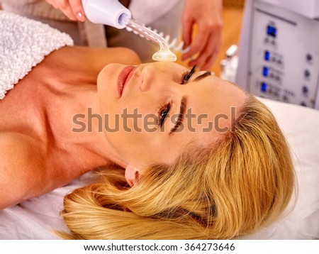 Young beautiful woman looking up receiving electric darsonval facial massage after procedure at beauty salon.  - stock photo