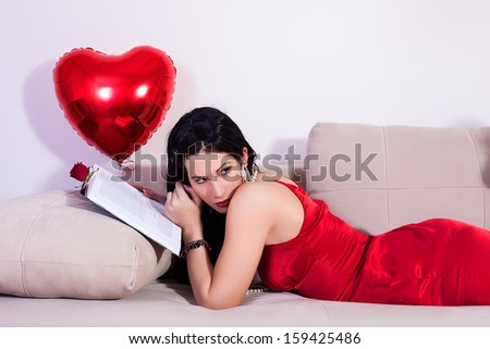 young beautiful woman lying down in bed. valentine day - stock photo