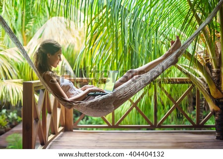 Young beautiful woman lying in a hammock with laptop in a tropical resort - stock photo