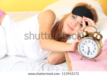 young beautiful woman lying on bed with eye mask and  alarm clock, on yellow background - stock photo