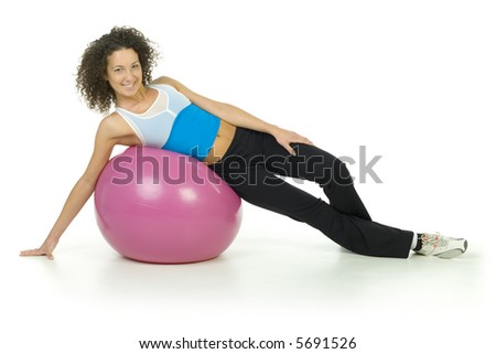 Young, beautiful woman lying on big pink ball. Smiling and looking at camera. Isolated on white in studio. Whole body, front view