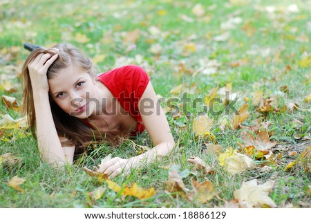 young beautiful woman lying on the green grass with maple leaf