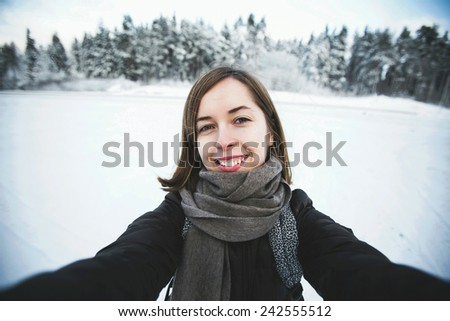 Young beautiful woman makes selfie portrait in snowy winter day in forest while backpack traveling across Russia - stock photo