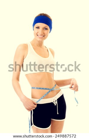 Young beautiful woman measuring waist with a tape measure, health and dieting concept - stock photo