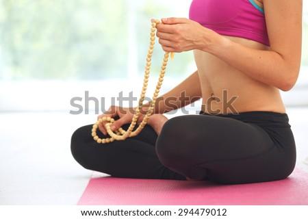 Young beautiful woman meditating in lotus pose. - stock photo