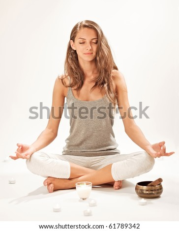 Young beautiful woman meditating in lotus pose - stock photo