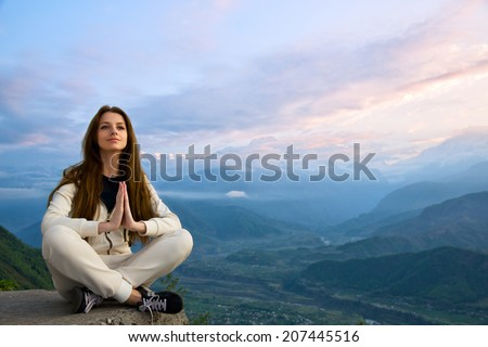 Young beautiful woman meditating in The Himalayas mountains at sunrise - stock photo