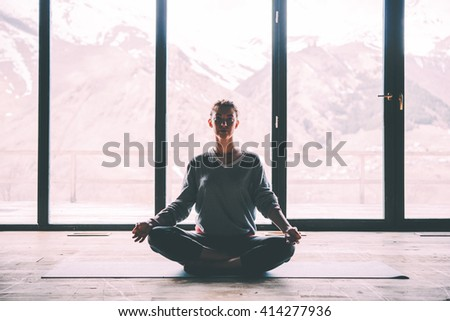 Young beautiful woman meditating while practicing yoga with mountain view in the background. Freedom concept. Calmness and relax, woman happiness. Toned picture - stock photo