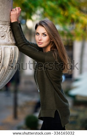 young beautiful woman model dressed in a warm green cardigan posing outside in a city park - stock photo