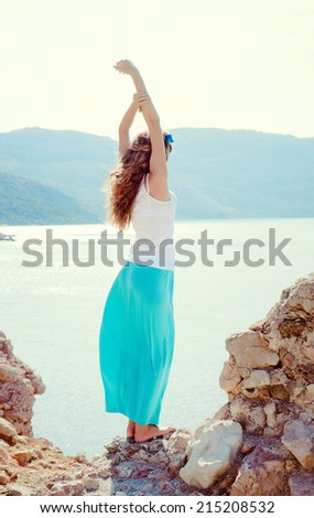 young beautiful woman near the sea with his arms raised
