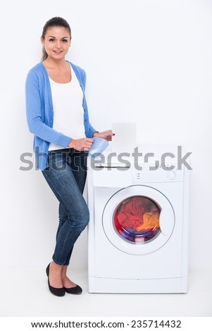 Young beautiful woman near the washing machine with detergent on a white background. - stock photo