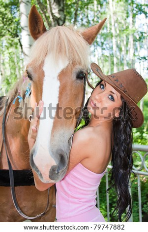 young beautiful woman next to a horse on nature