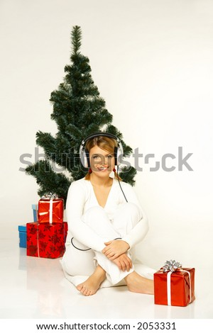 Young beautiful woman next to christmas tree and presents listen to music in headphones