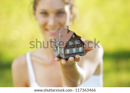 Young beautiful woman offering a house - stock photo