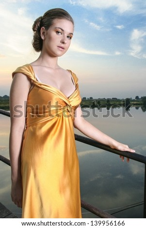 Young beautiful woman on a pier at the sunset - stock photo