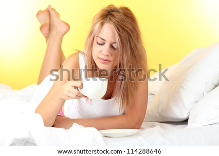 young beautiful woman on bed with cup of coffee on yellow background - stock photo