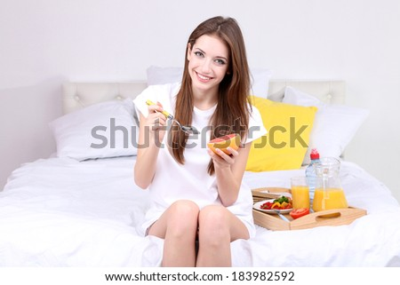 Young beautiful woman on bed with light breakfast