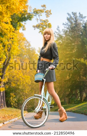 Young beautiful woman on bicycle at autumn park - stock photo