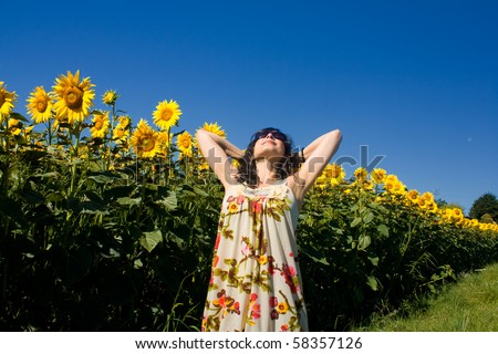 young beautiful woman on field in summer - stock photo