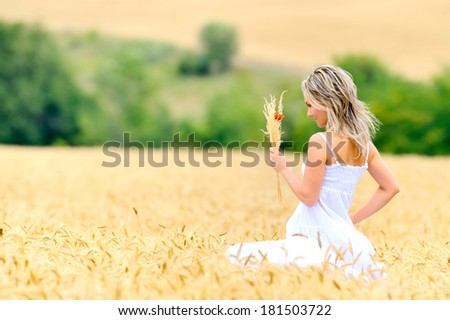 young beautiful woman on golden field in summer - stock photo