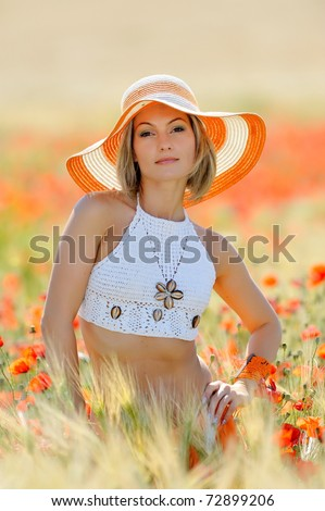 young beautiful woman on golden wheat field in summer - stock photo