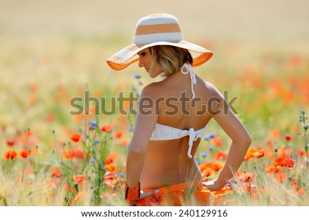 young beautiful woman on golden wheat field in summer sunny day - stock photo