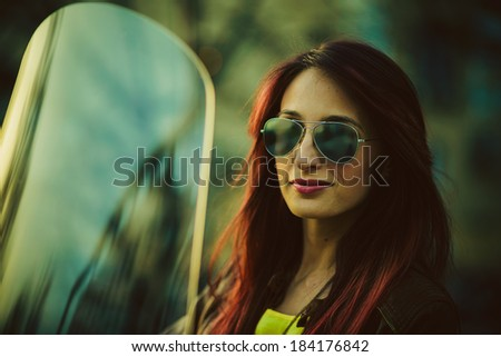Young beautiful woman on motorcycle - stock photo