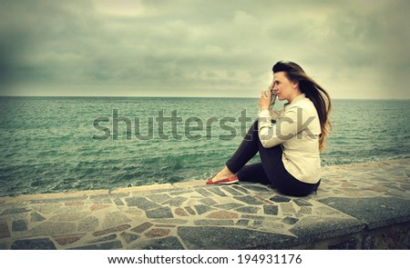 Young beautiful woman on sea background - stock photo