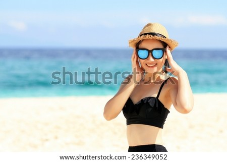 Young beautiful woman on the beach, Beautiful girl in sunglasses with hands near face on background of the sea and blue sky.