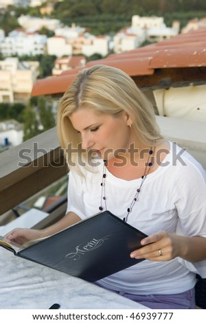 Young beautiful woman on vacation is looking in menu in small restaurant with a view on the sea - stock photo