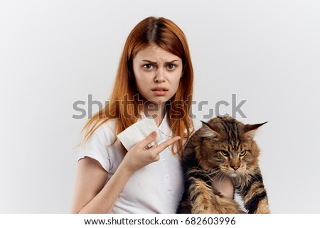 Young beautiful woman on white isolated background holds a cat.