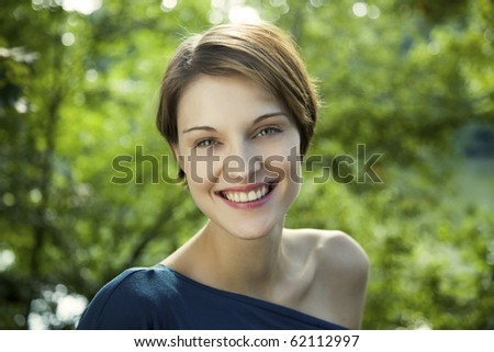 young beautiful woman outdoor at a lake with green enviroment - stock photo