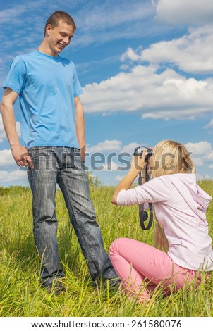 Young beautiful woman photographs man against background of green summer meadows.