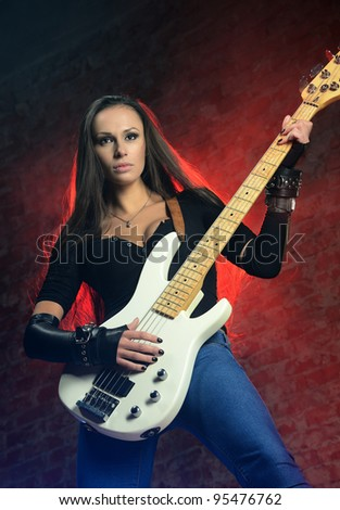 Young beautiful woman playing the guitar - stock photo