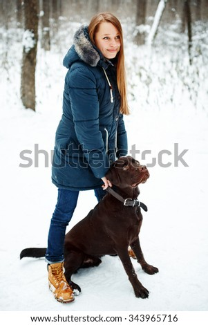 Young Beautiful Woman Playing with Her Dog in Winter Park. Lifestyle Concept, Winter Activities. - stock photo