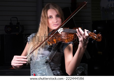 Young beautiful woman plays music on violin
