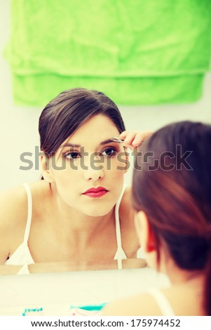 Young beautiful woman plucking her eyebrows with tweezers at her bathroom - stock photo