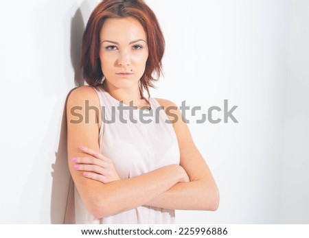 young beautiful woman portrait on white posing in short and white dress - stock photo
