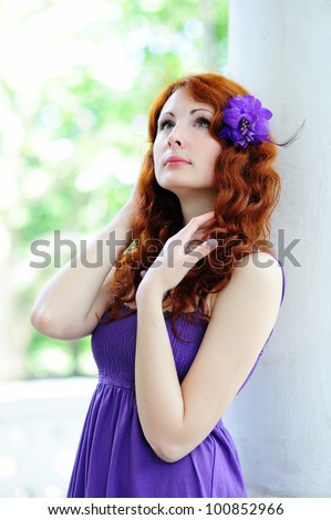 Young beautiful woman portrait with flower in her hair. Outdoor. - stock photo