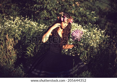 young beautiful woman portrait with flowers in field summer day retro colors - stock photo