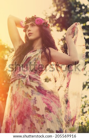 young beautiful woman portrait with wreath of flowers in field summer day retro colors - stock photo